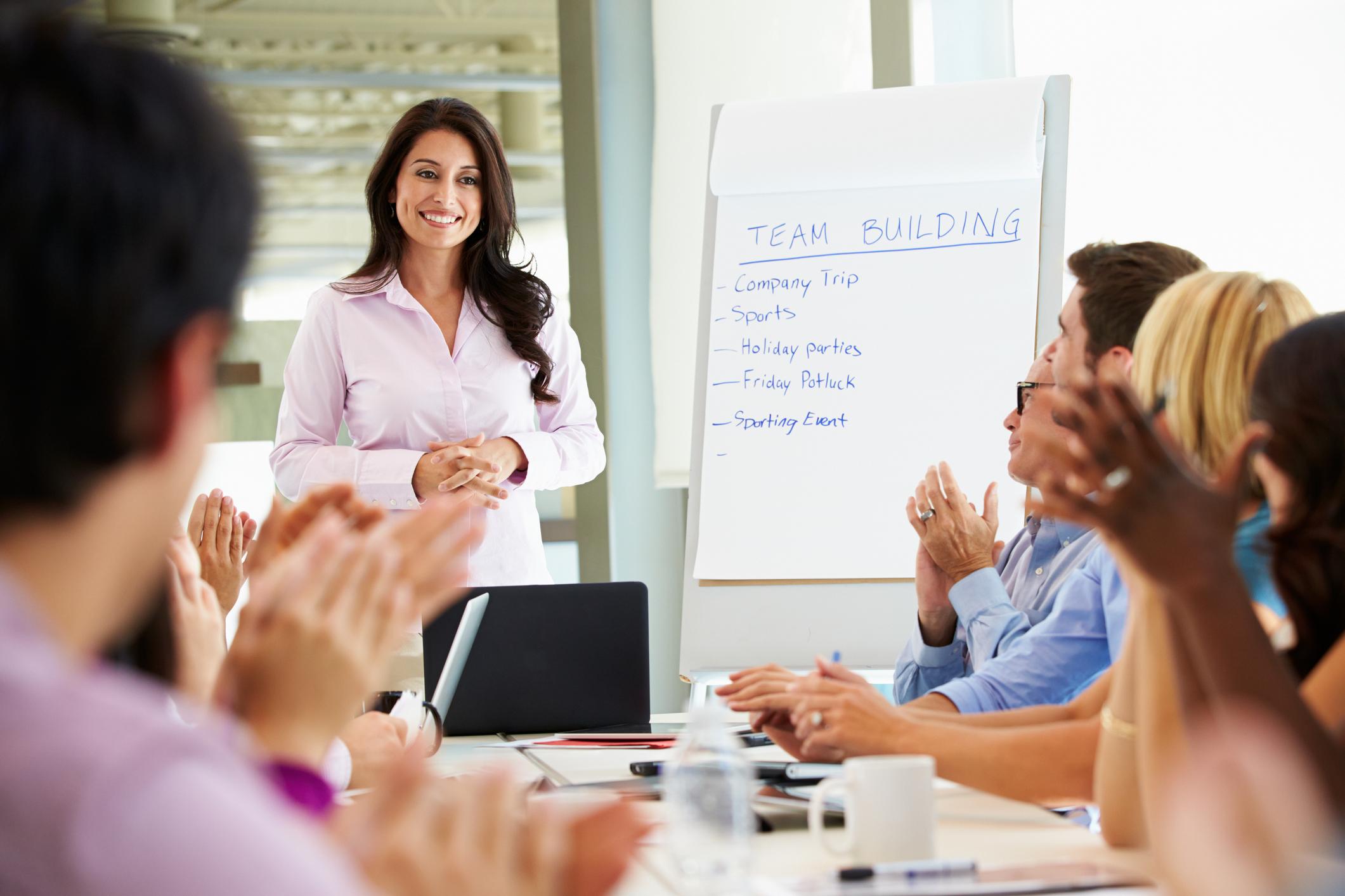 Businesswoman Addressing Meeting Around Boardroom Table In Smart/Casual Dresswear